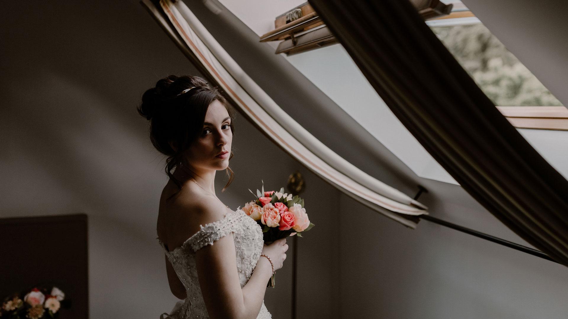 La mariée entrain de regarder l'objectif avec son bouquet dans les mains. Shooting d'inspiration mariage Corail et Gold. Perfect Moment by A Wedding planner Reims