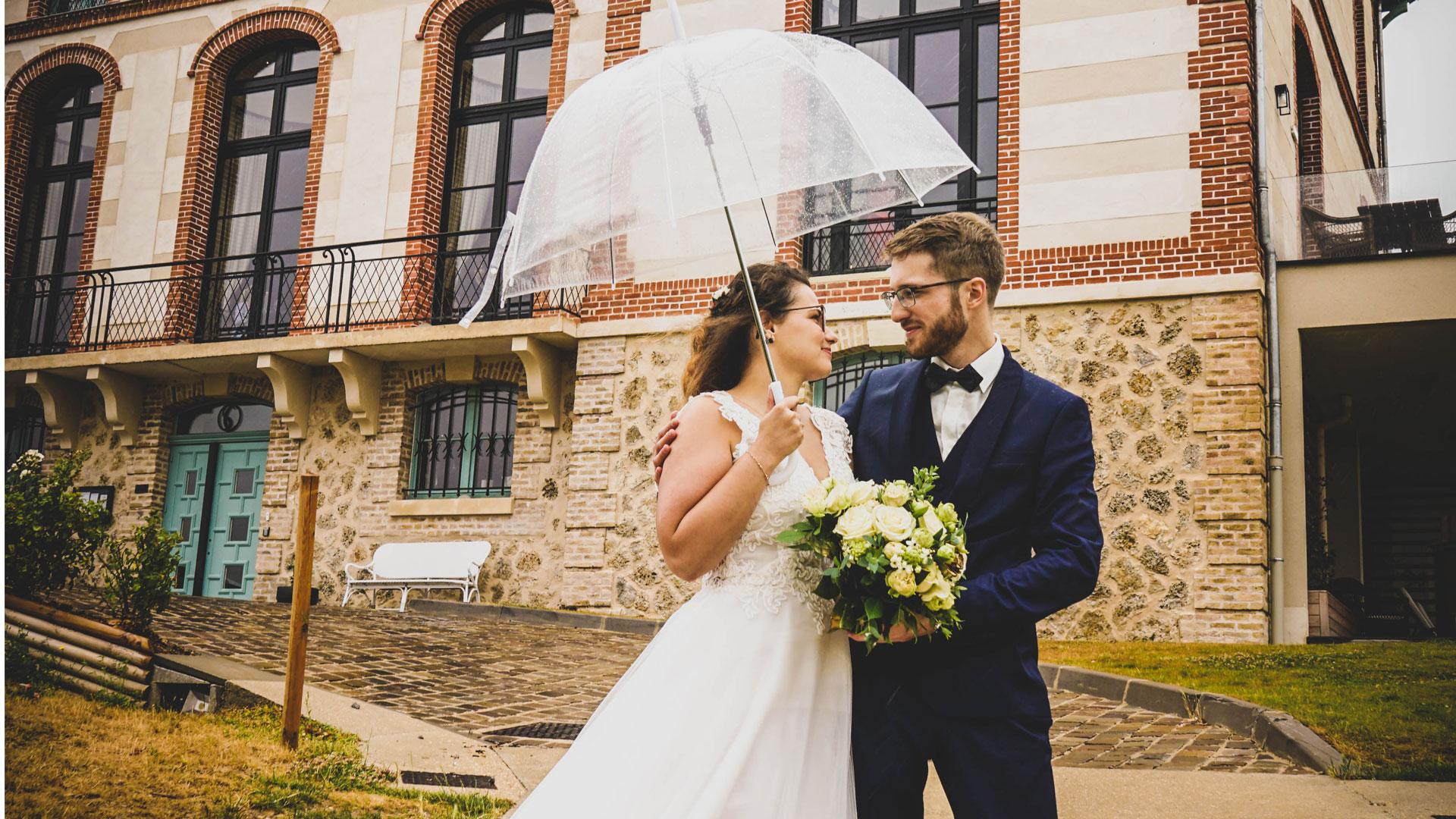 Les mariés sous la pluie avec un parapluie transparent. Perfect Moment by A Wedding planner Reims